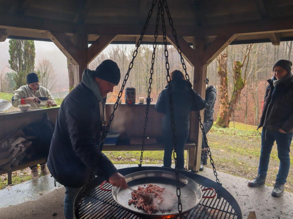 Männer, Grill, Schwenkgrill, Feuer, Lagerfeuer, Kochen, grillen, Freundschaft, Freunde, Gemeinschaft, Waldhütte, Unterstand